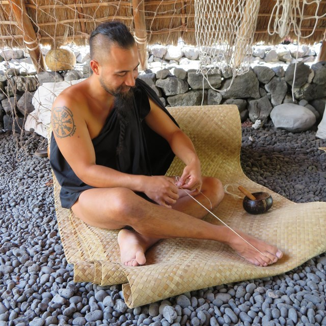 Man in traditional clothing practices traditional rope making while seated on a lauhala mat.