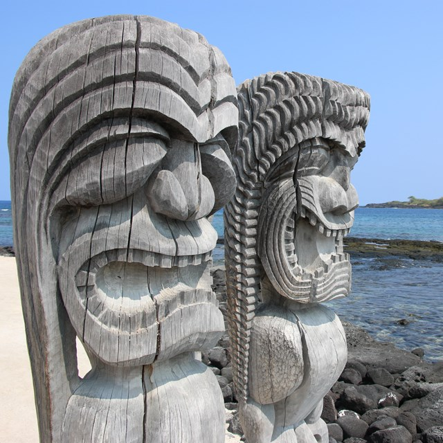 Two carved kiʻi images look out over the ocean