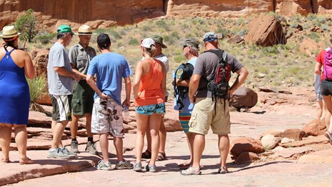 A group of people in summer clothes stands around a Park Ranger.