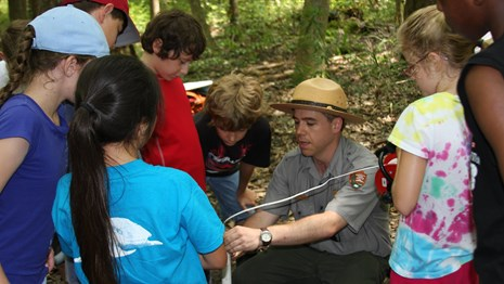 Ranger demonstrates groundwater monitoring techniques to a group of school children