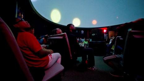 A child sitting with a crowd of people stares up at at the planetarium ceiling during a program.