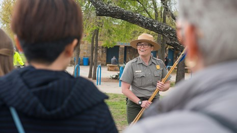 Park Ranger holds an atl atl as she gives presentation to elementary school students