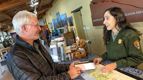 ranger helping visitor at front desk of visitor center