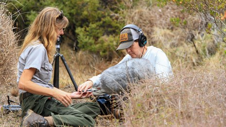 a female ranger sits with an audio technician in tall grass