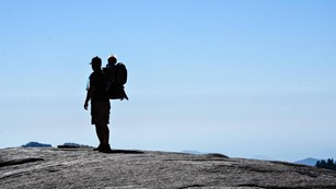 A hiker carries a tot in a backpack. Photo by Katie Kenig.