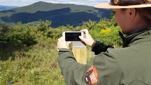 A female Park Ranger holds a phone up a bracket and takes a picture of the mountain layers beyond