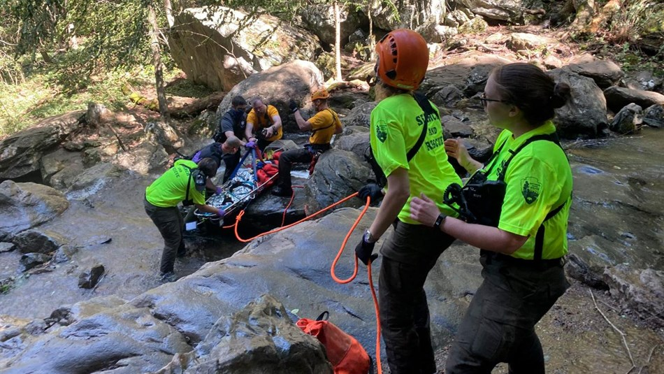 A rescue crew helps a visitor into a basket from the bottom of a waterfall, where they have fallen.