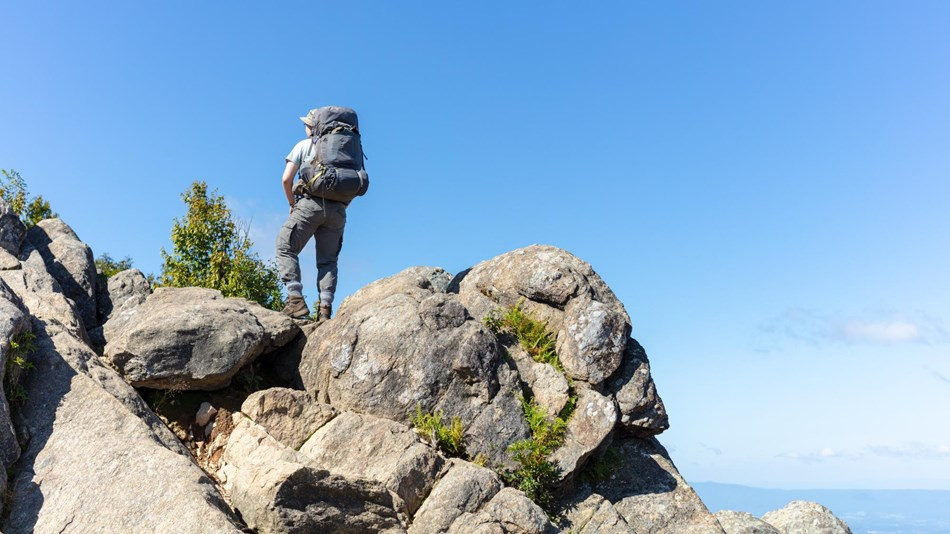 A man stands on top of a boulder, looking out over the view.
