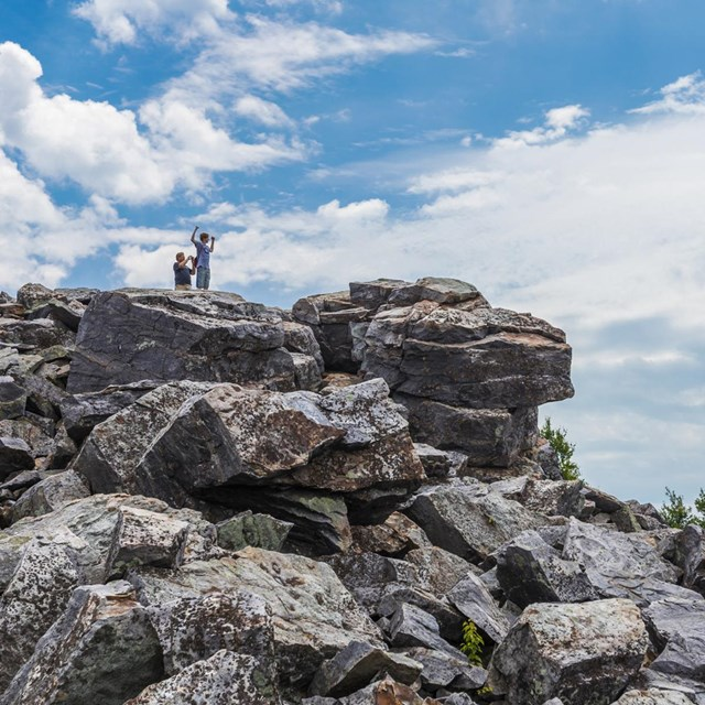 Two hikers stand on top of a large pile of rocks, looking out over a mountainous view.