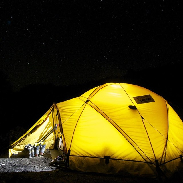 A yellow tent is set up in the middle of a dark night.