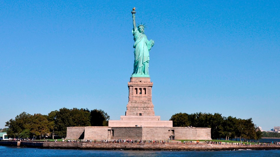 The Statute of Liberty and visitors can be seen across the water.