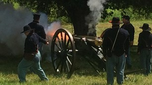 A Union cannon fires and flames belch from the muzzle.