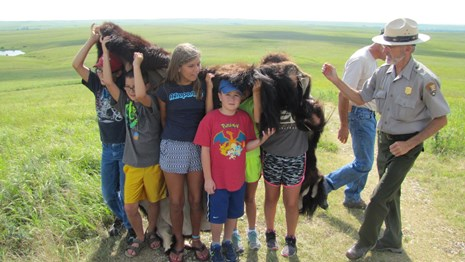 photo of kids trying on a bison hide, feeling its weight