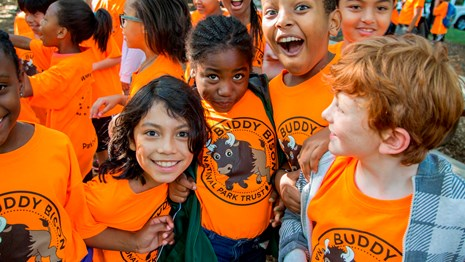 A group of smiling children in orange shirts