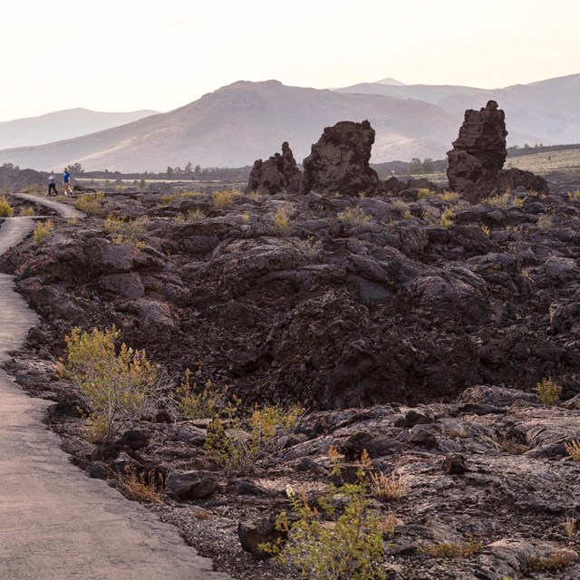 Hikers on a trail through lava flows