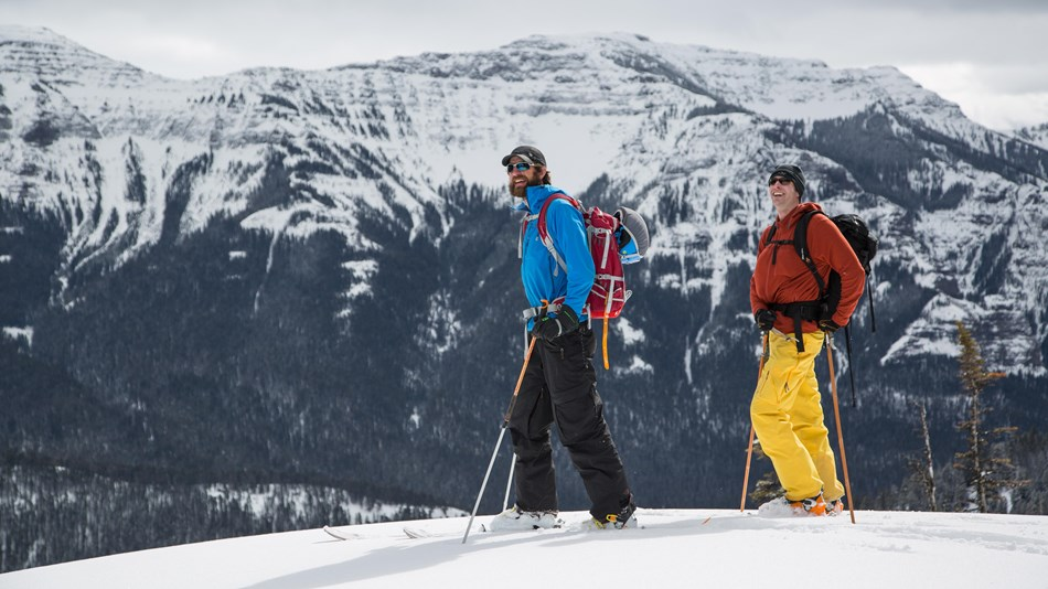 Two backcountry skiers look onward with mountain views in the background.