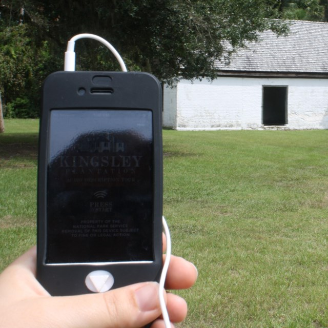 an audio tour device held by hand with historic barn in distance