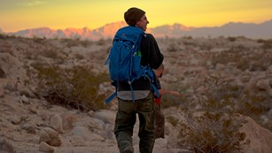 A hiker wearing a backpack on a trail at sunset.