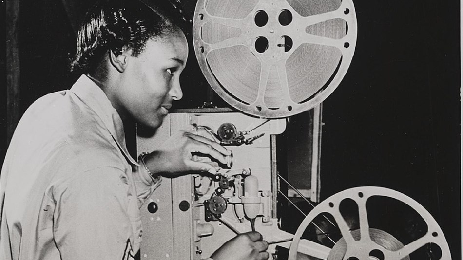 Photo of women working a projector.