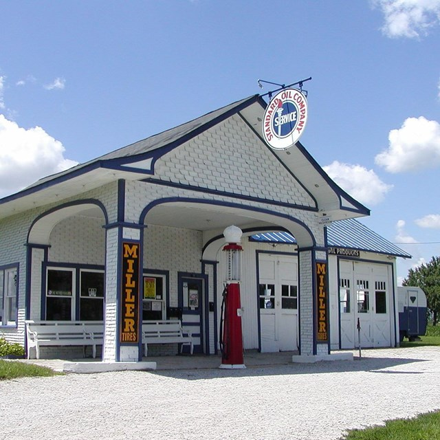 A white, wood, single room historic gas station under a blue sky.