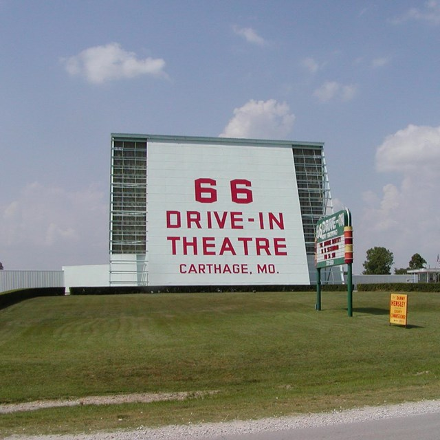 A large drive in theater screen with green grass in front.
