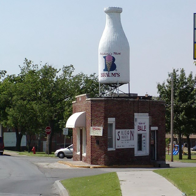 A small brick building with a giant milk bottle statue behind it.