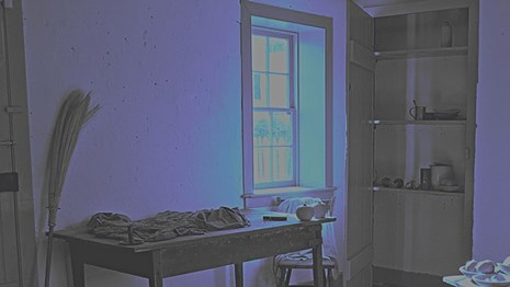 A photograph of the interior of slave quarters at Hampton NHS with a blue, monochrome filter.