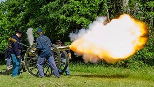 Park rangers and volunteers fire a 12 pound Napoleon cannon during a living history demonstration.