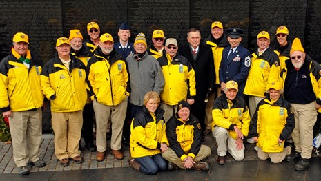 Volunteers pose for a photo in front of the Vietnam Veterans Memorial