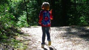 A child hiking on a forested trail in Whiskeytown NRA.