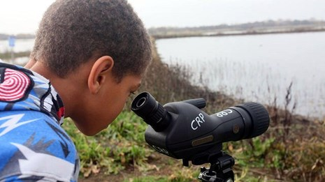 A young boy looks at the lansdcape through a telescope