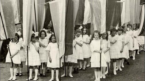 Image of young girls holding banners for suffrage. From cover of Junior Suffragist book