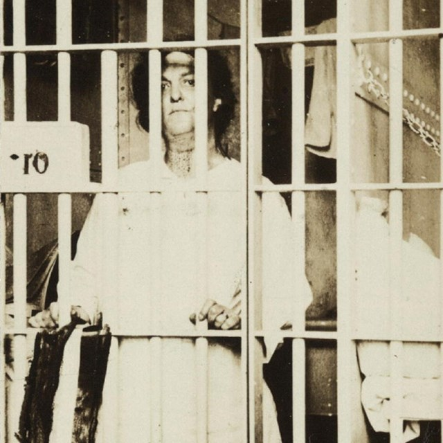 Photograph of Helena Hill Weed, facing forward, standing behind bars in a prison cell. LOC photo