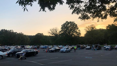 Cars parked in a parking lot as the sun sets.