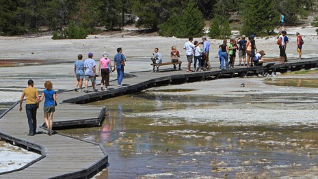 People walk along a boardwalk that goes through the a bare landscape covered in parts by water.