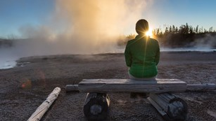 A person enjoys a sunset in the Norris Geyser Basin.