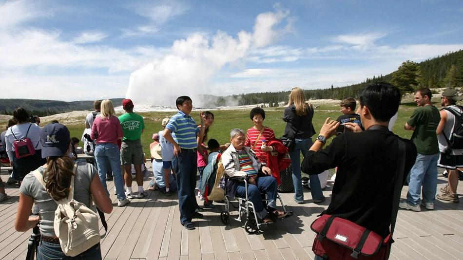 Wheelchair-bound visitor and his family take a picture while Old Faithful Geyser erupts.