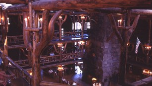 Gnarled wooden posts hold up the second floor balcony with the stone fireplace visible below.