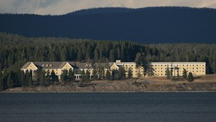 Bright yellow, three-story hotel building standing in the conifer forest next to a deep, blue lake.