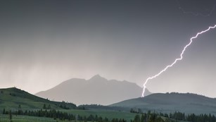Lightning strikes Electric Peak as a dark storm rolls over the mountain.