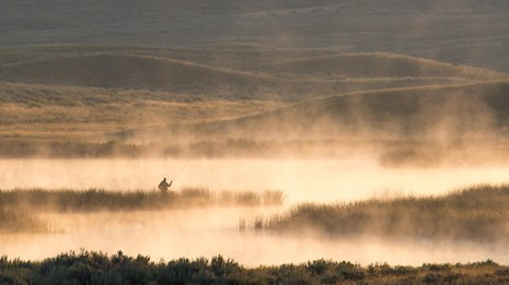 Angler fishing in Yellowstone during a golden morning.