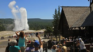 People sitting and standing on a wooden patio taking pictures of an erupting geyser.