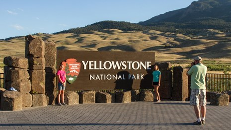 Two girls stand in front of a large Yellowstone National Park sign while their dad photographs them