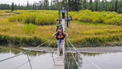 Hikers crossing a creek via a cable suspension bridge.