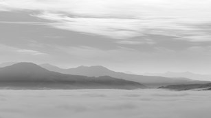 Black and white photograph of low-lying clouds and distant mountain peaks.