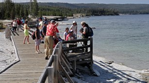 A park ranger stands on a boardwalk along a lakeshore and talks with visitors.
