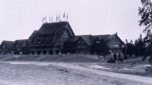 Black and white photograph of the log cabin structure of the Old Faithful Inn.