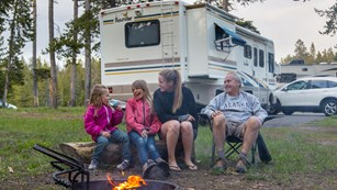 Four people sitting in campsite in front of a fire laughing and smiling.
