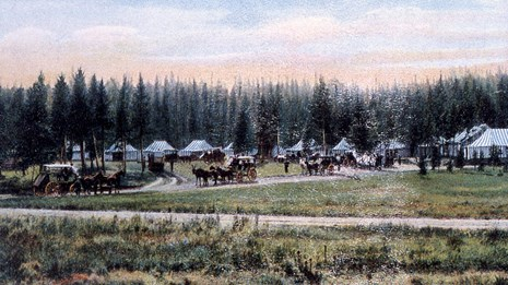 An historic postcard of a large tent camp and stage coaches