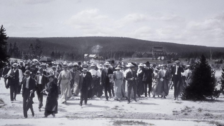 A historical photo of a group of people walking across a geyser runoff channel.